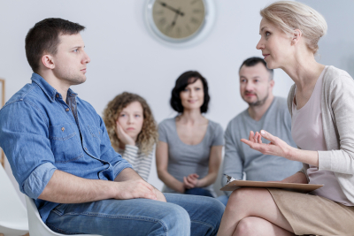 upset man sitting in group therapy and listening to the psychologist with concerned family