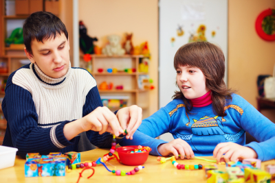 happy kids with special needs develop their fine motor skills in daycare rehabilitation center